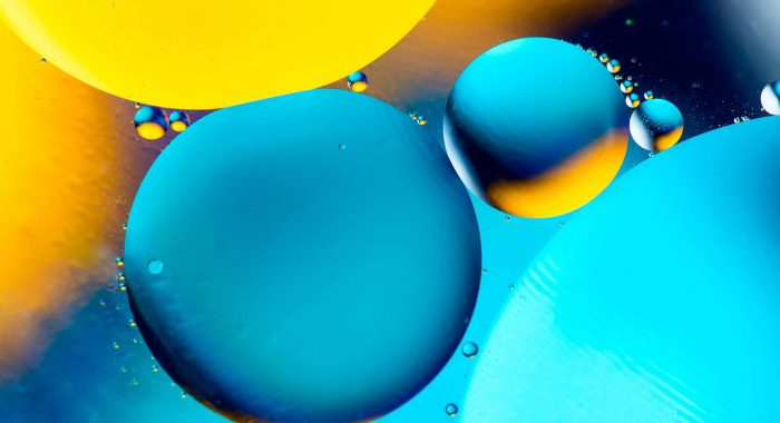 Beautiful color abstract background from mixied water and oil. Pastel colored abstraction. Orange, blue and yellow background from water bubbles