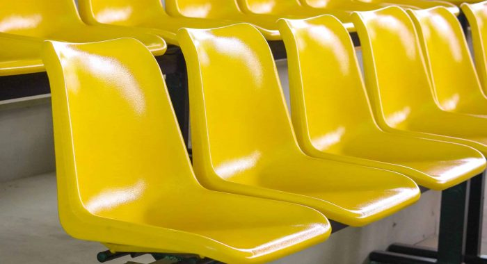 Empty plastic yellow seats row at stadium indoor show or sport field place background.