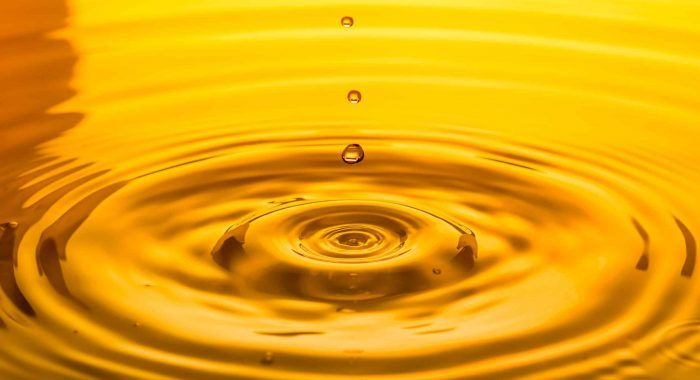 close up of a drop oil on a yellow background