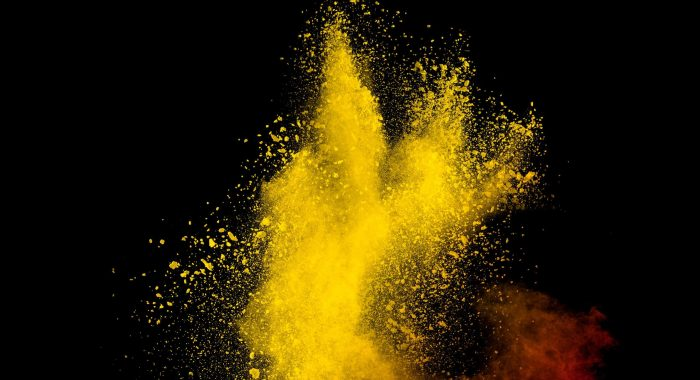 Yellow red powder explosion cloud on black background. Freeze motion of color dust  particles splashing.
