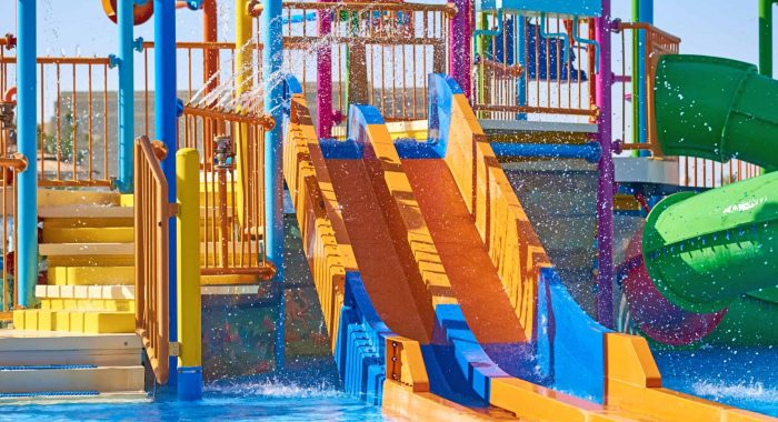 Colorful slides in waterpark close up. Aquapark sliders with pool