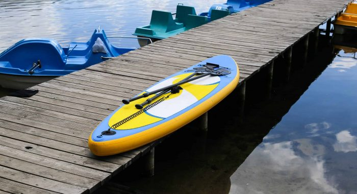 Stand up paddle board on pier near river. Sup board, inflatable SUP board
