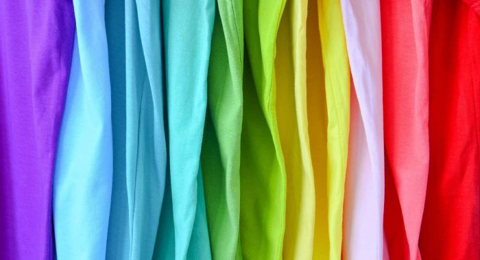 close up collection of colorful rainbow t-shirts hanging on clot